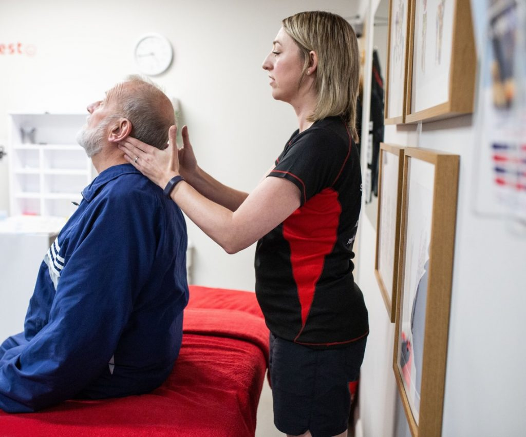 physiotherapist assesses neck range of movement