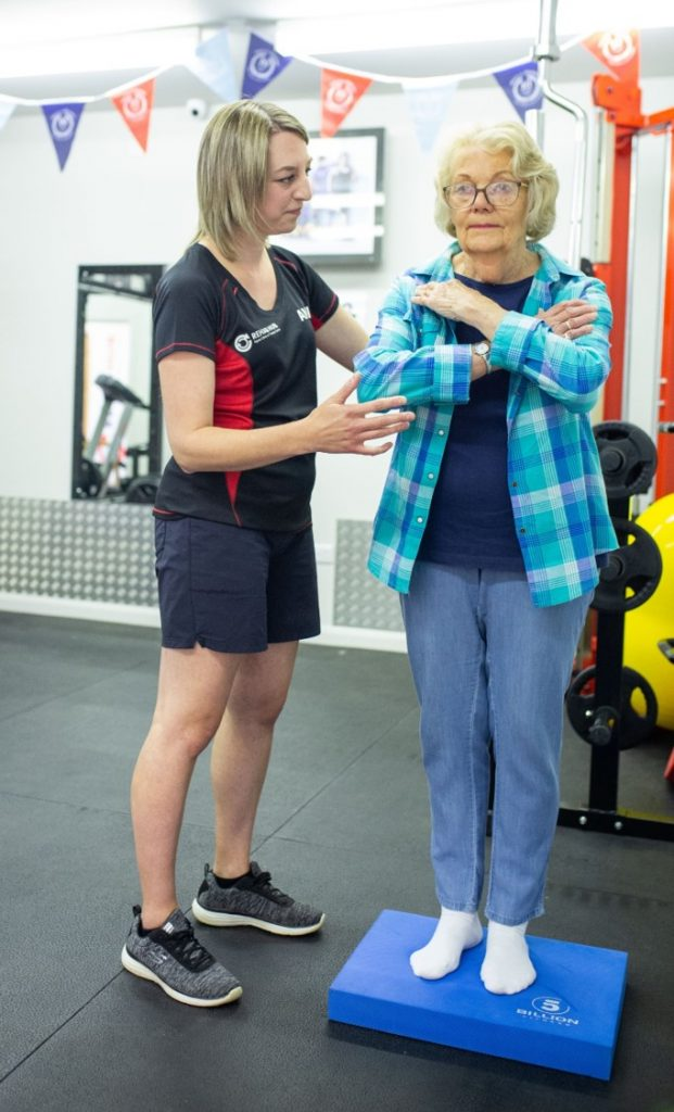 physiotherapist supervises balance exercise of senior lady