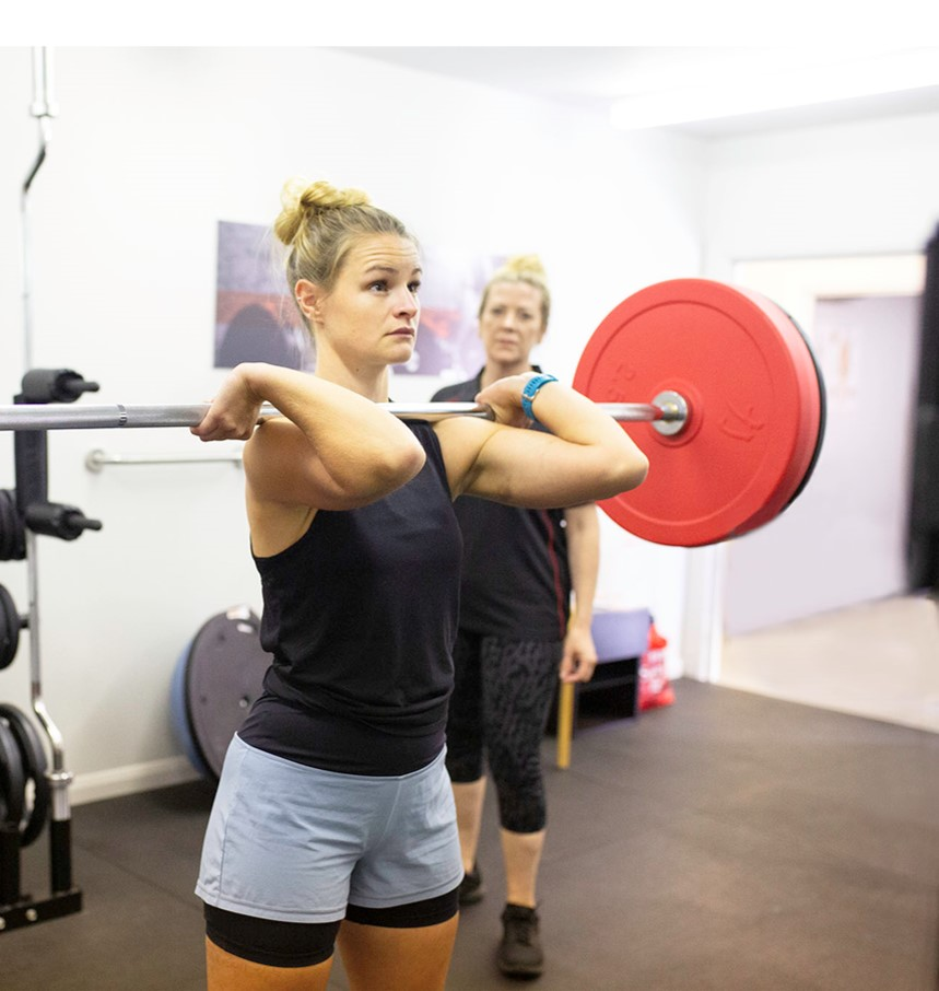 sports therapist supervises weightlifting in biggleswade