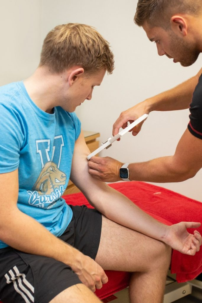 sports nutritionist doing fat analysis caliper testing on man