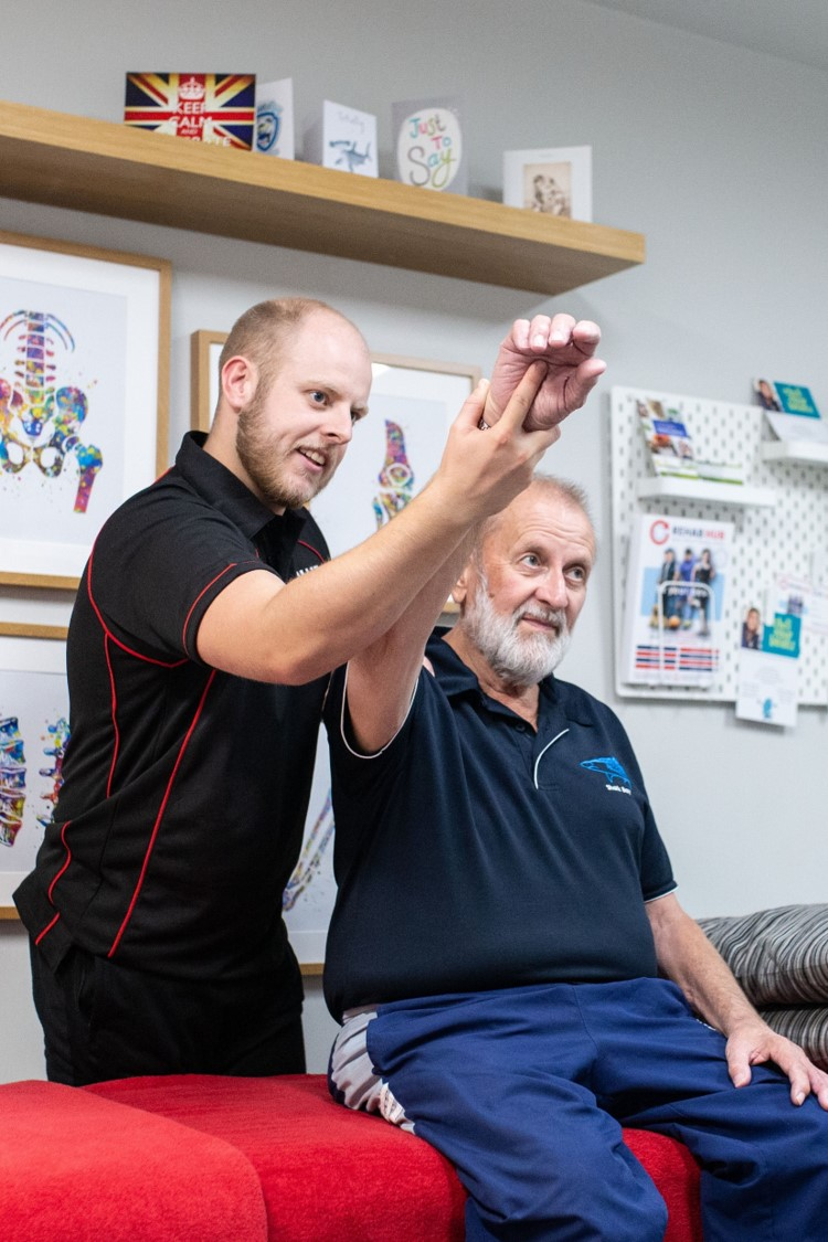 osteopath assesses shoulder movement in biggleswade