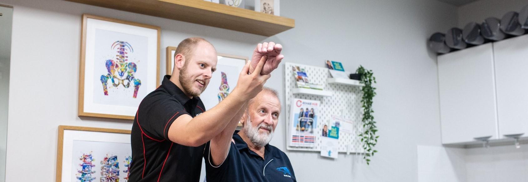 osteopath assesses a patient's shoulder