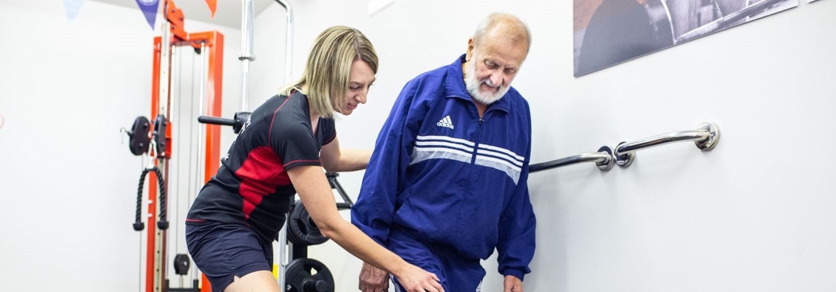 physiotherapist provides knee exercise for senior man