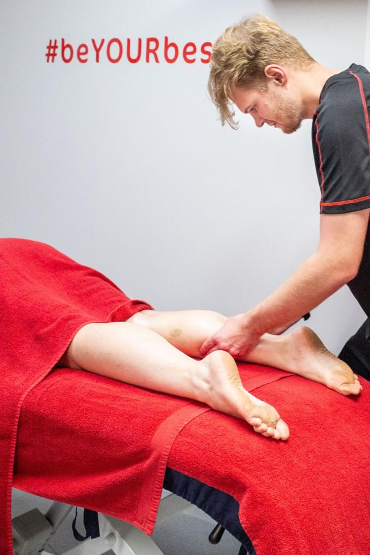 sports massage therapist treats calf strain