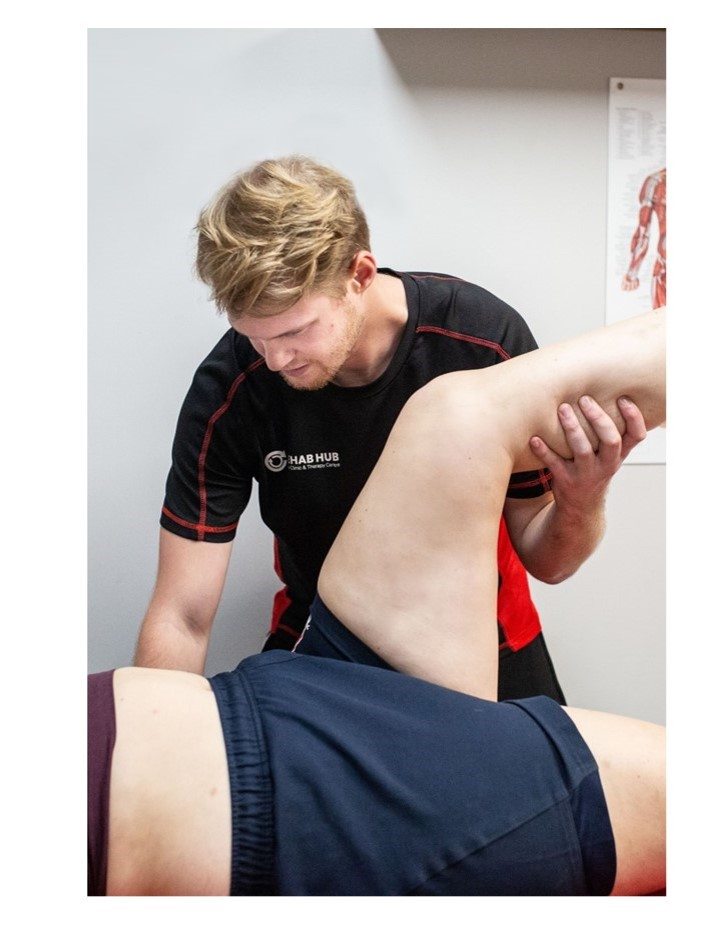 sports therapist stretching a patient's leg